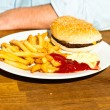 Junk food on wooden table. Fast food. French fries and hamburger with mayonaise and ketchup. — Stock Photo