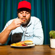 Man with beard eating fast food meal. Enjoying french fries and a hamburger. Trucker with red cap. — Stock Photo #11597646
