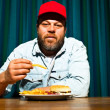 Man with beard eating fast food meal. Enjoying french fries and a hamburger. Trucker with red cap. — Stock Photo #11597652