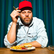 Man with beard eating fast food meal. Enjoying french fries and a hamburger. Smoking a cigar. Trucker with red cap. — Stock Photo #11597675