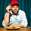 Mwith beard eating fast food meal. Enjoying french fries and hamburger. Smoking cigar. Trucker with red cap. — Stock Photo #11597675