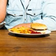 Junk food on wooden table. Fast food. French fries and hamburger with mayonaise and ketchup. — Stock Photo #11597676