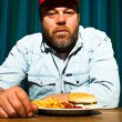 Man with beard eating fast food meal. Enjoying french fries and a hamburger. Trucker with red cap. — Stock Photo #11597684