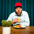 Man with beard eating fast food meal. Enjoying french fries and a hamburger. Trucker with red cap. — Stock Photo #11597687