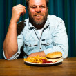 Man with beard eating fast food meal. Enjoying french fries and a hamburger. — Stock Photo