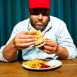 Man with beard eating fast food meal. Enjoying french fries and a hamburger. Trucker with red cap. — Stock Photo #11597695