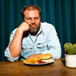 Stock Photo: Man with beard eating fast food meal. Enjoying french fries and a hamburger.