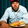 Man with beard eating fast food meal. Enjoying french fries and a hamburger. Trucker with red cap. — Stock Photo #11597715