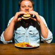 Royalty-Free Stock Photo: Man with beard eating fast food meal. Enjoying french fries and a hamburger.