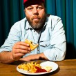 Stock Photo: Man with beard eating fast food meal. Enjoying french fries and a hamburger. Trucker with red cap.