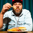 Man with beard eating fast food meal. Enjoying french fries and a hamburger. Trucker with red cap. — Stock Photo #11597730