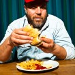 Man with beard eating fast food meal. Enjoying french fries and a hamburger. Trucker with red cap. — Stock Photo #11597733