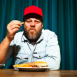 Man with beard eating fast food meal. Enjoying french fries and a hamburger. Trucker with red cap. — Stock Photo #11597736