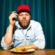 Man with beard eating fast food meal. Enjoying french fries and a hamburger. Smoking a cigar. Trucker with red cap. — Stock Photo