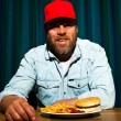 Man with beard eating fast food meal. Enjoying french fries and a hamburger. Trucker with red cap. — Stock Photo #11597741