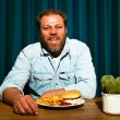 Man with beard eating fast food meal. Enjoying french fries and a hamburger. — Stock Photo #11597744