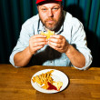 Man with beard eating fast food meal. Enjoying french fries and a hamburger. Trucker with red cap. — Stock Photo #11597752