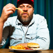 Man with beard eating fast food meal. Enjoying french fries and a hamburger. Trucker with red cap. — Stock Photo #11597759