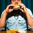 Man with beard eating fast food meal. Enjoying french fries and a hamburger. — Foto de Stock