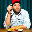 Man with beard eating fast food meal. Enjoying french fries and a hamburger. Smoking a cigar. Trucker with red cap. — Stock Photo #11597787