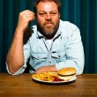 Man with beard eating fast food meal. Enjoying french fries and a hamburger. — 图库照片