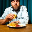 Man with beard eating fast food meal. Enjoying french fries and a hamburger. Trucker with red cap. — Stock Photo #11597793