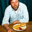 Man with beard eating fast food meal. Enjoying french fries and a hamburger. Trucker with red cap. — Stock Photo #11597801