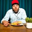Man with beard eating fast food meal. Enjoying french fries and a hamburger. Trucker with red cap. — Stock Photo #11597805
