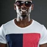 Cool urban stylish black american man. Fashion studio portrait isolated on grey background. Wearing dark sunglasses. Smiling. — Stock Photo #11644881