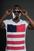 Cool urban stylish black american man. Fashion studio portrait isolated on grey background. Wearing dark sunglasses. — Stock Photo