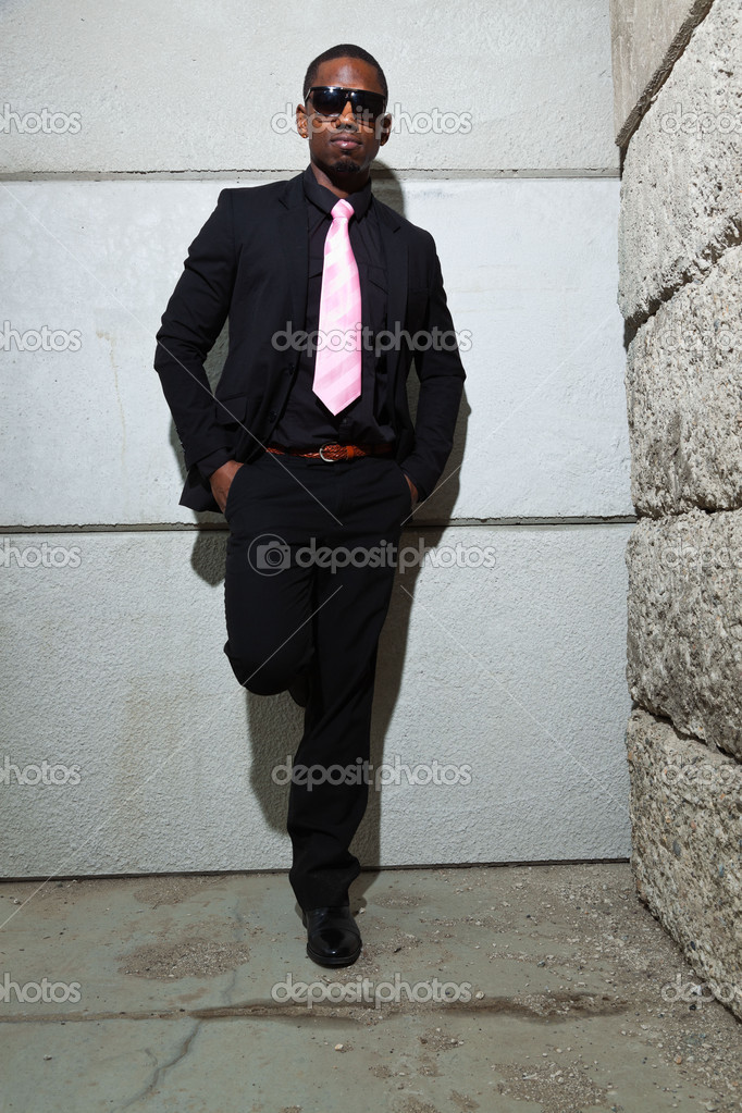 Cool black american man in dark suit wearing sunglasses. Fashion shot in urban setting. — Stock Photo #11644867