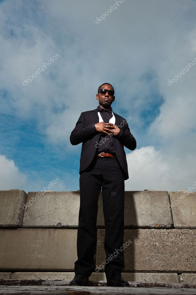 Cool black american man in dark suit wearing sunglasses. Fashion shot in urban setting. Blue cloudy sky. — Stock Photo #11644902