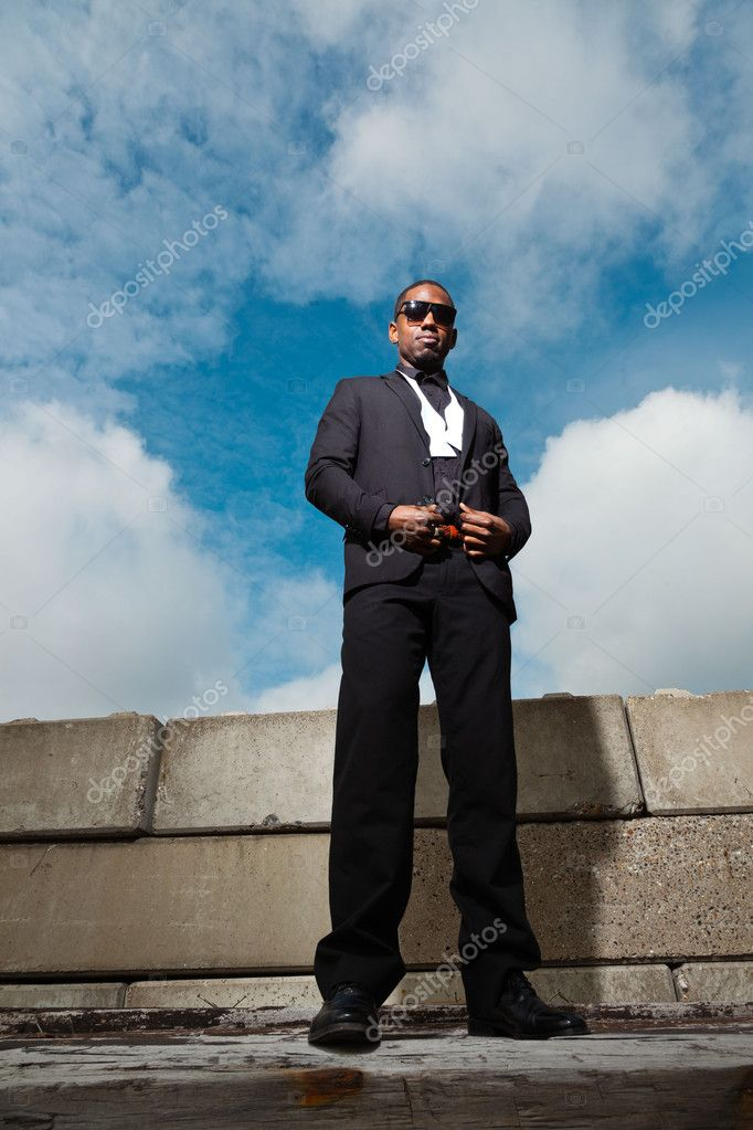 Cool black american man in dark suit wearing sunglasses. Fashion shot in urban setting. Blue cloudy sky. — Stock Photo #11644917