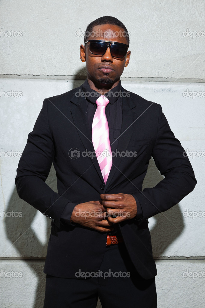 Cool black american man in dark suit wearing sunglasses. Fashion shot in urban setting. — Stock Photo #11645045