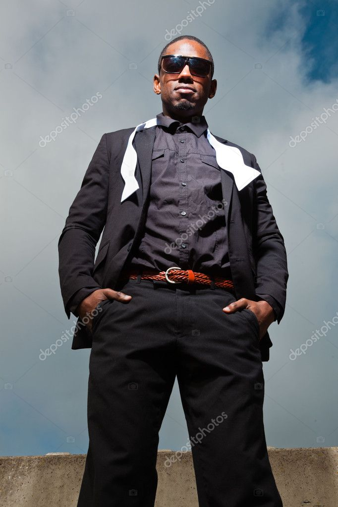 Cool black american man in dark suit wearing sunglasses. Fashion shot in urban setting. Blue cloudy sky. — Stock Photo #11645083