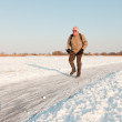Dutch winter landscape with senior skater on frozen lake. Blue clear sky. Retired man. — Stock Photo #11650949