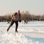 Dutch winter landscape with senior skater on frozen lake. Blue clear sky. Retired man. — Stock Photo