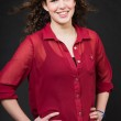 Smiling pretty girl with long brown curly hair. Fashion studio portrait isolated against black background. Wearing red shirt. — Stock Photo #11658068
