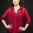 Pretty girl with long brown curly hair. Fashion studio portrait isolated against black background. Wearing red shirt. — Stock Photo