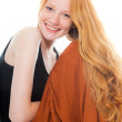 Smiling pretty girl with long red hair wearing black shirt and brown dress. Fashion studio shot isolated on white background. — Stock Photo #11742460
