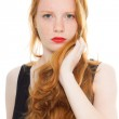 Pretty girl with long red hair and lipstick wearing black shirt. Fashion studio shot isolated on white background. — Stock Photo #11742513