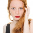 Pretty girl with long red hair and lipstick wearing black shirt. Fashion studio shot isolated on white background. — Stock Photo