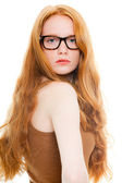 Pretty girl with long red hair wearing brown shirt and vintage glasses. Fashion studio shot isolated on white background. — Stock Photo