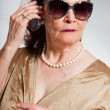 Stock Photo: Portrait of good looking senior woman wearing sunglasses with expressive face showing emotions. Calling with cell phone. Acting young. Studio shot isolated on grey background.