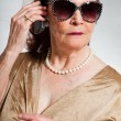 Portrait of good looking senior woman wearing sunglasses with expressive face showing emotions. Calling with cell phone. Acting young. Studio shot isolated on grey background. — Stock Photo