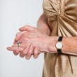 Closeup of hands of senior woman wearing a watch and ring. Studio shot isolated on grey. — Stock Photo #11898310