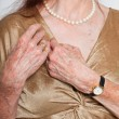 Closeup of hands of senior woman wearing a watch and ring. Studio shot. - Stock Photo