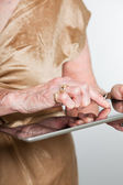Hands of a senior woman using a tablet. Studio shot on grey background. — Stock Photo