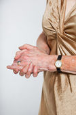 Closeup of hands of senior woman wearing a watch and ring. Studio shot isolated on grey. — Stock Photo