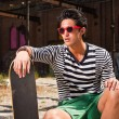 Royalty-Free Stock Photo: Urban asian man with red sunglasses and skateboard sitting on street. Good looking. Cool guy. Wearing blue white striped sweater and green shorts. Old neglected building in the background.